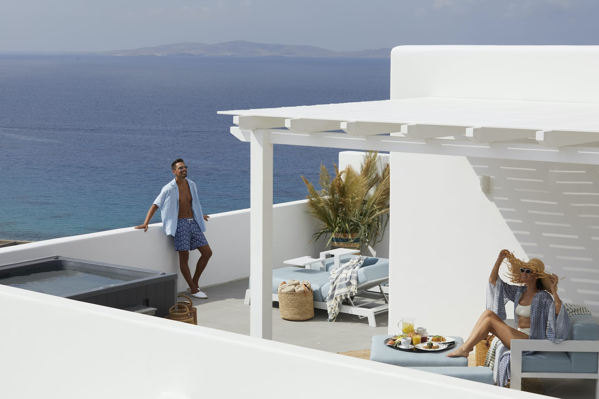Couple enjoying the private terrace with panoramic views of the Aegean sea at their Junior Suite.