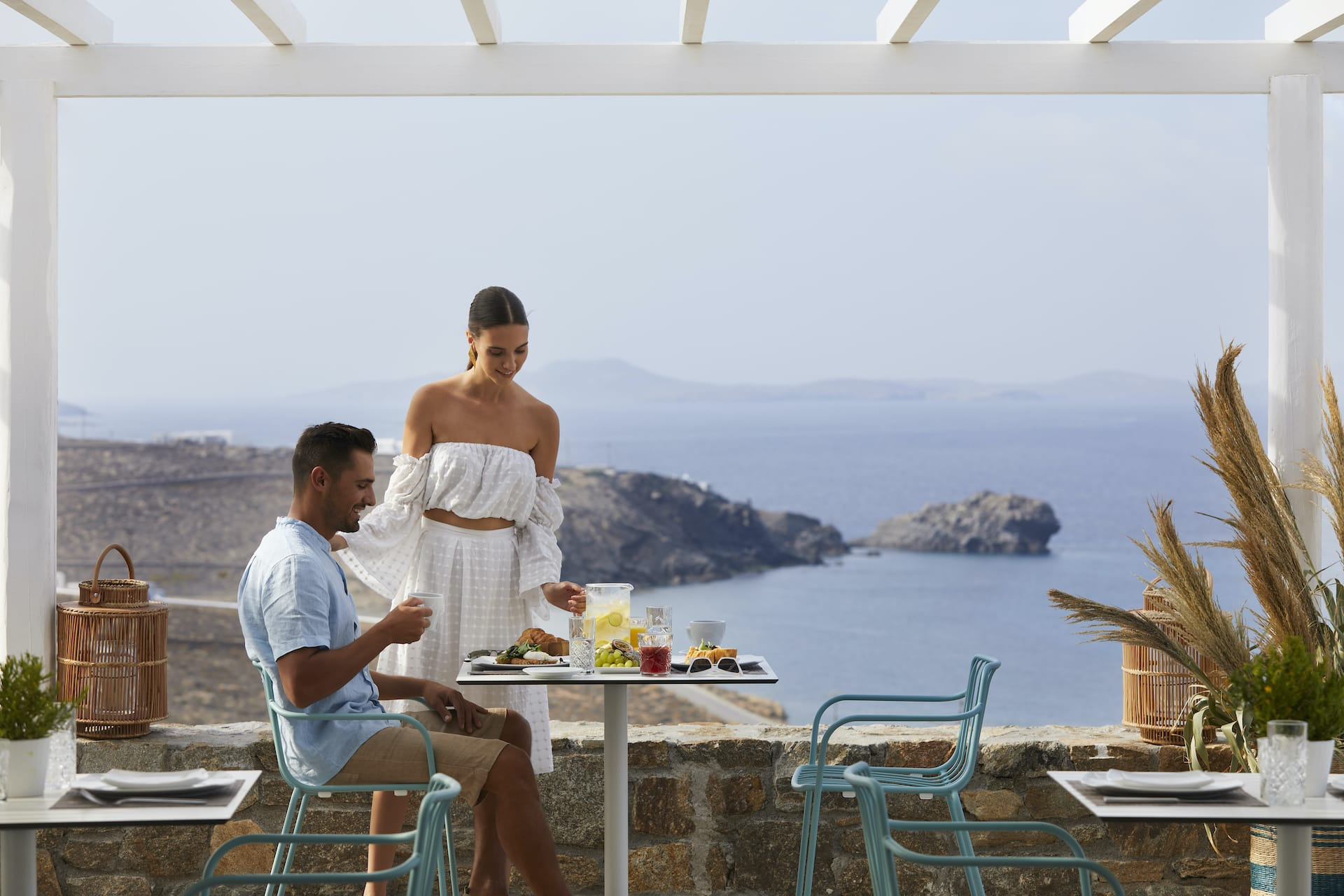 Couple enjoying their breakfast at the Epic Blue Mykonos hotel. Woman serving man juice.