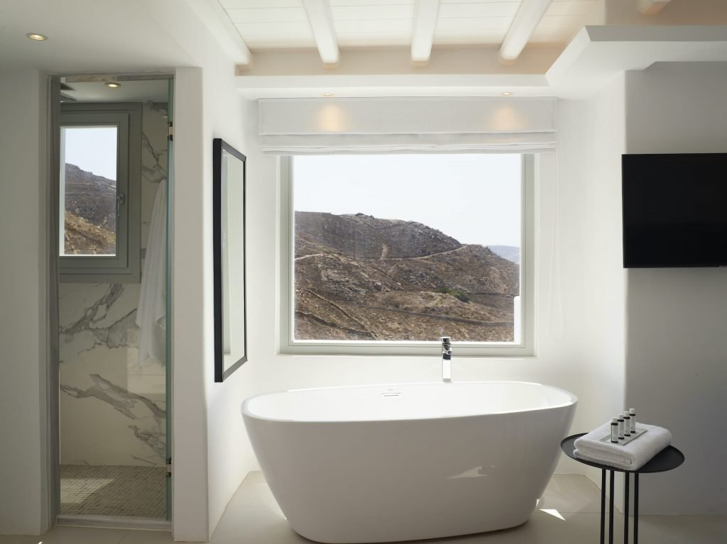 The freestanding bathtub with direct sea views of the Executive Suite of the Epic Blue Mykonos.