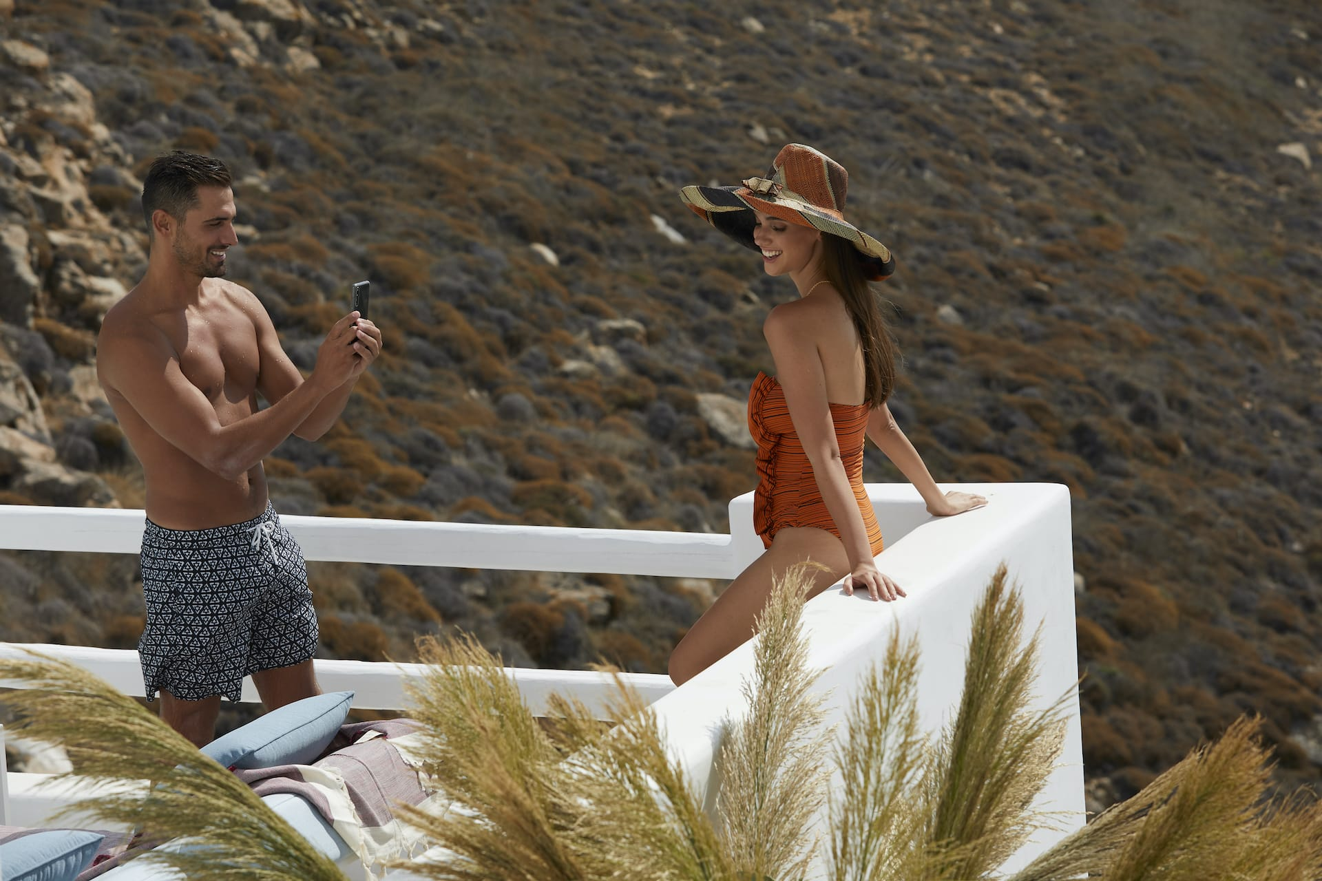 Beautiful couple taking photos while staying at the Epic Blue luxury hotel in Houlakia, Mykonos.