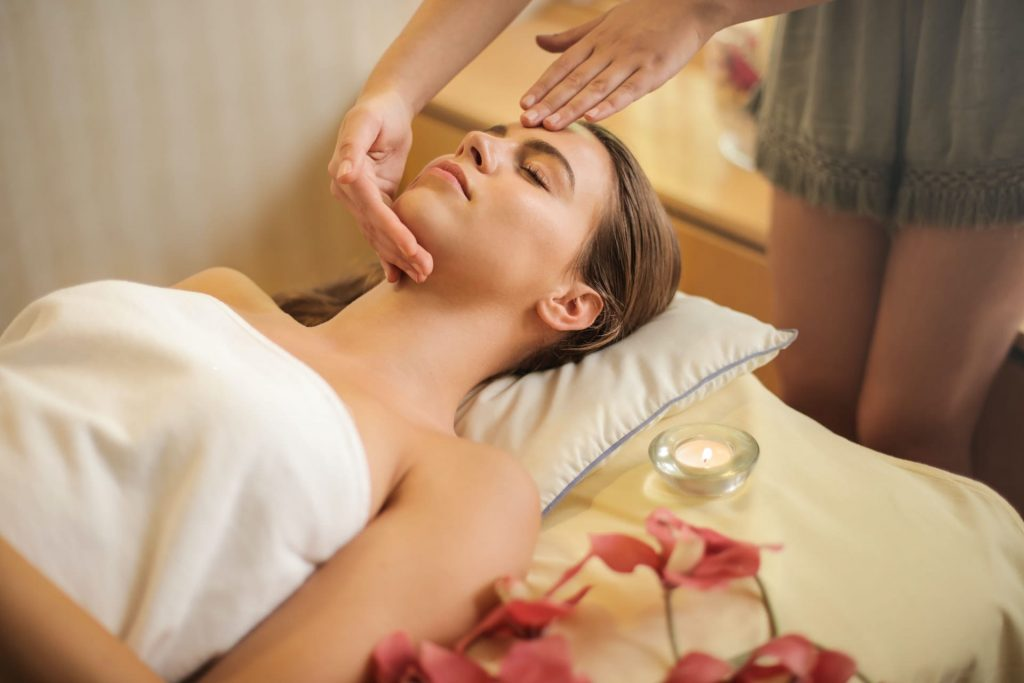 Spa & Wellness in Houlakia, Mykonos. Woman enjoying a facial treatment lying on a bed.